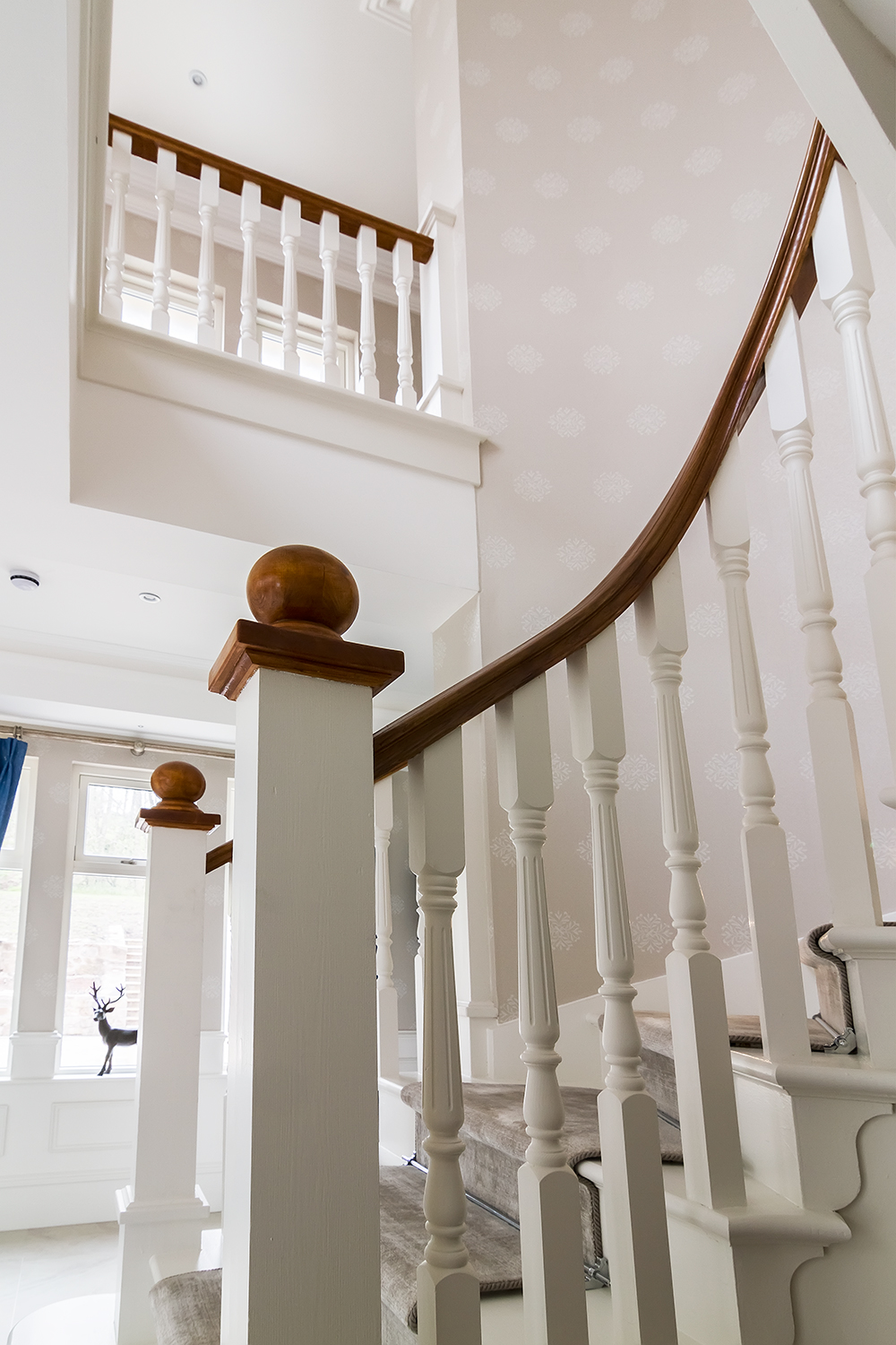 www.stockwell-ltd.co.uk   Bespoke curved cut-stringer staircase with white oak lacquered curved handrail and newel caps. This stair is highly detailed with stringer capes, curved scotia beading and double curtail steps.