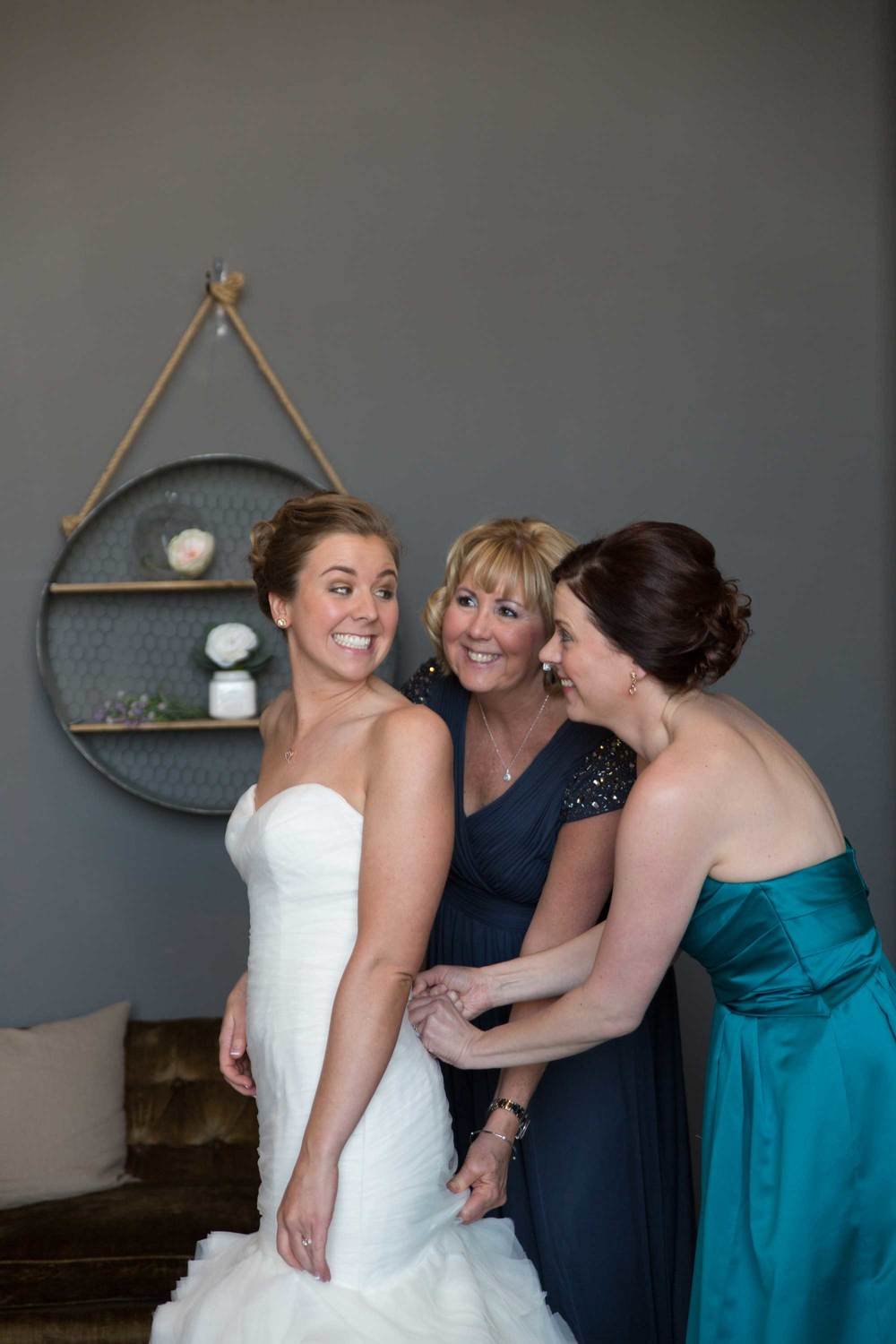 3. ALL SMILES AS OUR BRIDE'S MOM & MAID OF HONOR LACES UP HER DRESS.