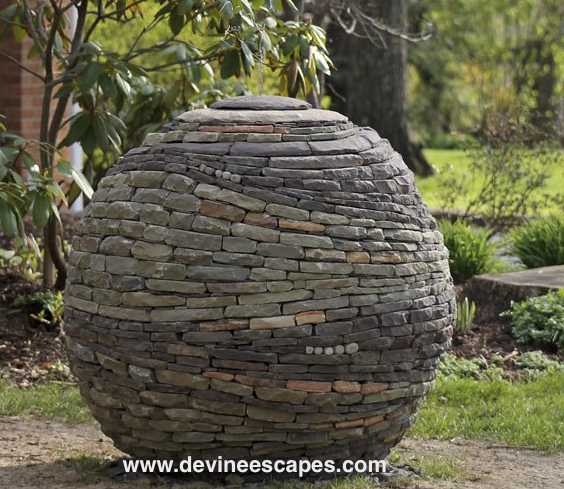 """A ball of living energy, made from multiple colors of stone swirling about,"" is how Devin Devine describes this garden art sculpture of a large 4-foot sphere created with various colored stone stacked and arranged in a circular eddy of waves.This stone sphere is  typically held together with no mortar or cement, and is  a challenge to assemble."