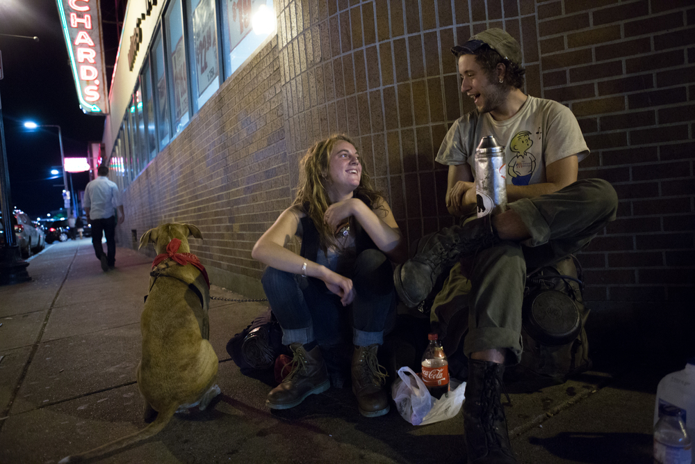Two homeless 20-year-olds who asked to be identified as Toby (left) and Anchor (right) sit outside Blanchard's liquor store in Allston where they asked pedestrians for money and alcohol with their dog, Venus. The couple had recently traveled from Colorado by hitching rides on cargo trains. Photo credit: Justin Saglio