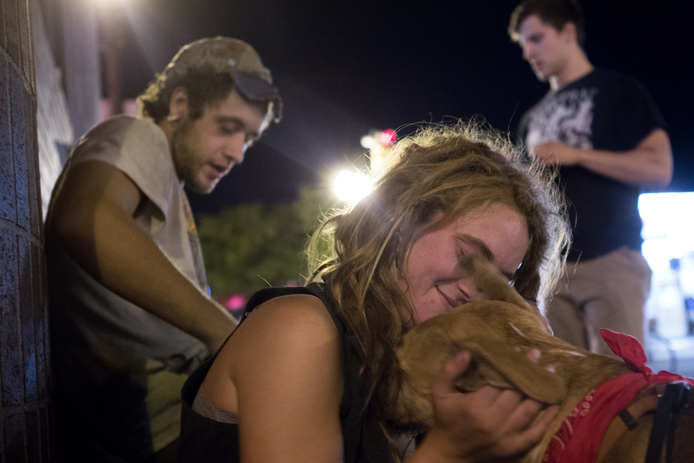 A 20-year-old homeless woman who asked to be identified as Toby embraces her dog, Venus, outside Blanchard's liquor store in Allston, Mass. where she had been asking pedestrians for money and alcohol. Photo credit: Justin Saglio