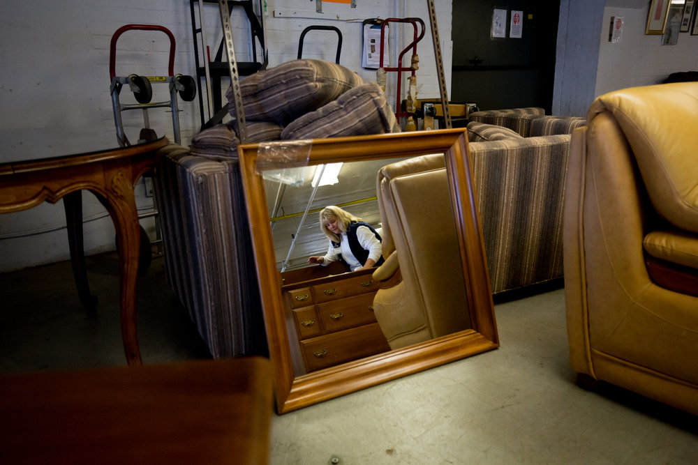 Nov. 25, 2017 - Renee LeBlanc is reflected while cleaning a dresser at  New Life Bank Furniture in Walpole, Mass., which provides furniture to families in need.