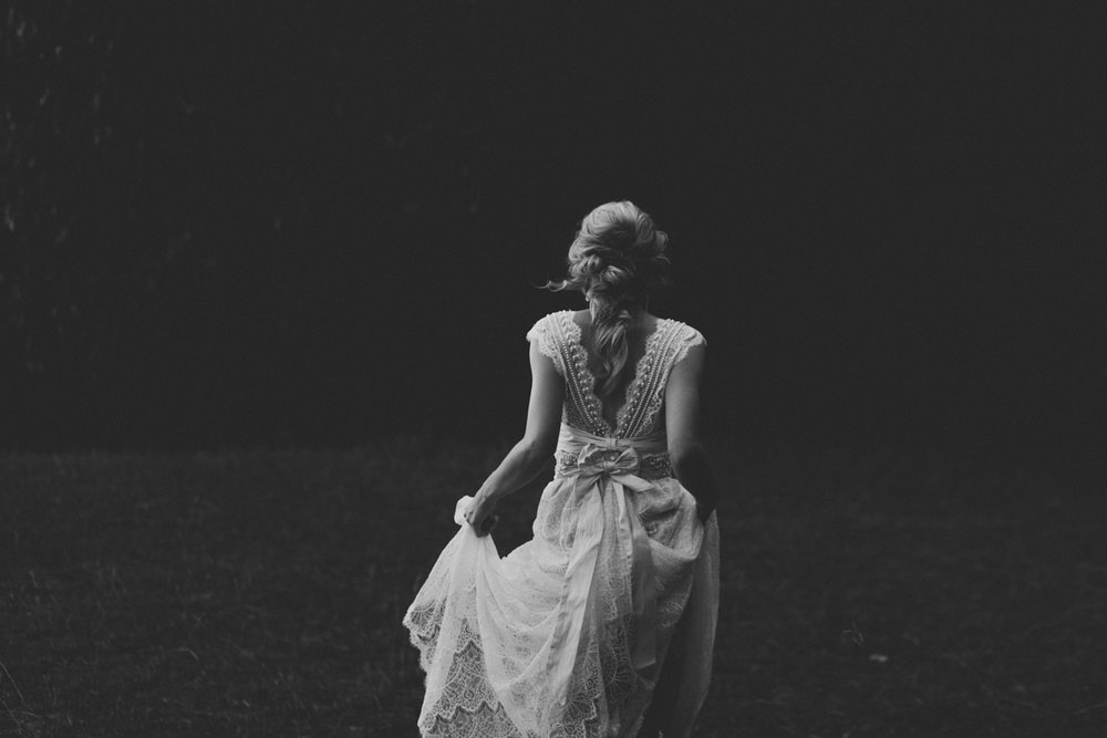 Bride walking through field in an Anna Campbell wedding dress provided by Wildflower Bridal in Asheville, NC.