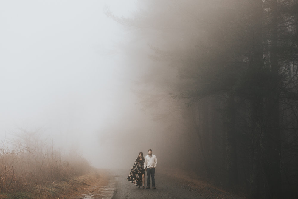Couple walking down a gravel road on Max Patch mountain in the fog.