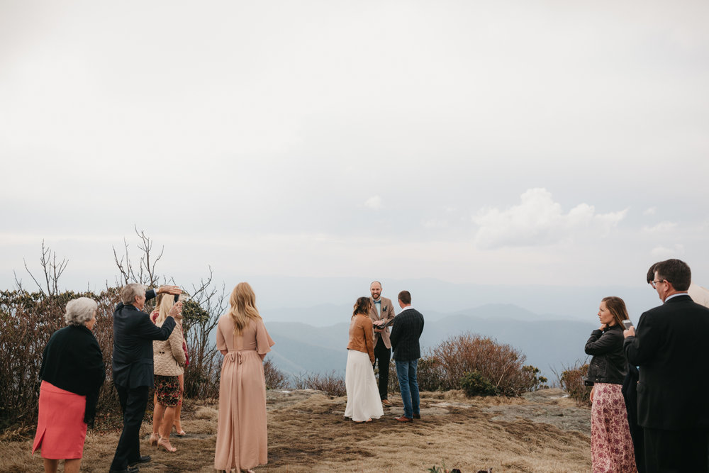 Couple exchanges vows at Craggy Pinnacle on the Blue Ridge Parkway during an elopement ceremony.