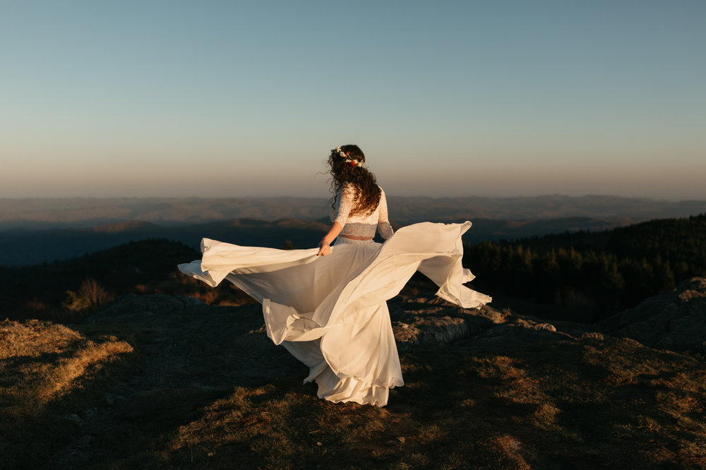 Woman in wedding dress at sunset on Black Balsam mountain in Asheville, NC.