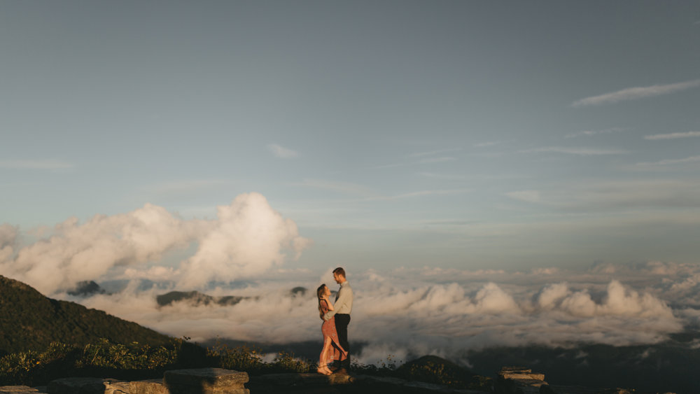 Couple embraces on a mountaintop above the clouds at Craggy Pinnacle in North Carolina.