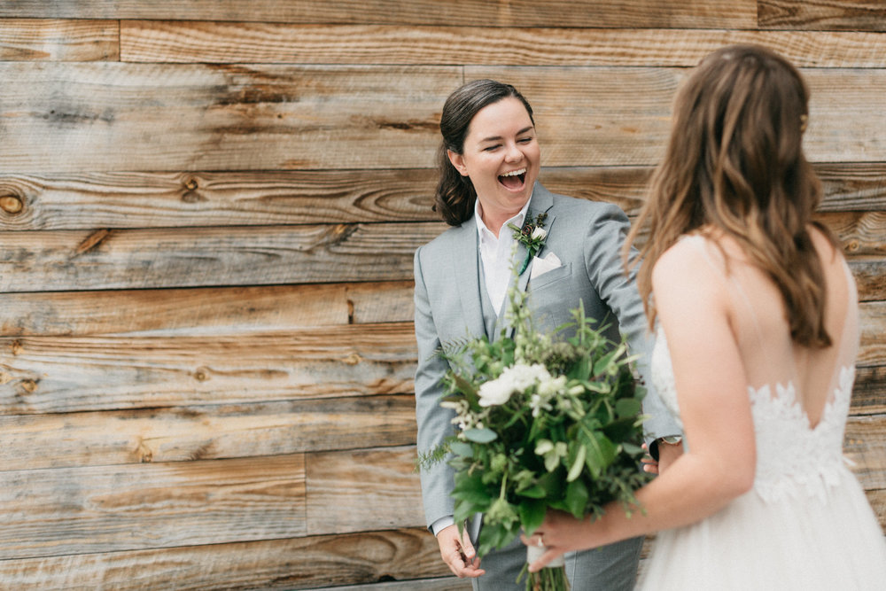 Brides share a first look on their wedding day at the Cloth Mill at Eno River.