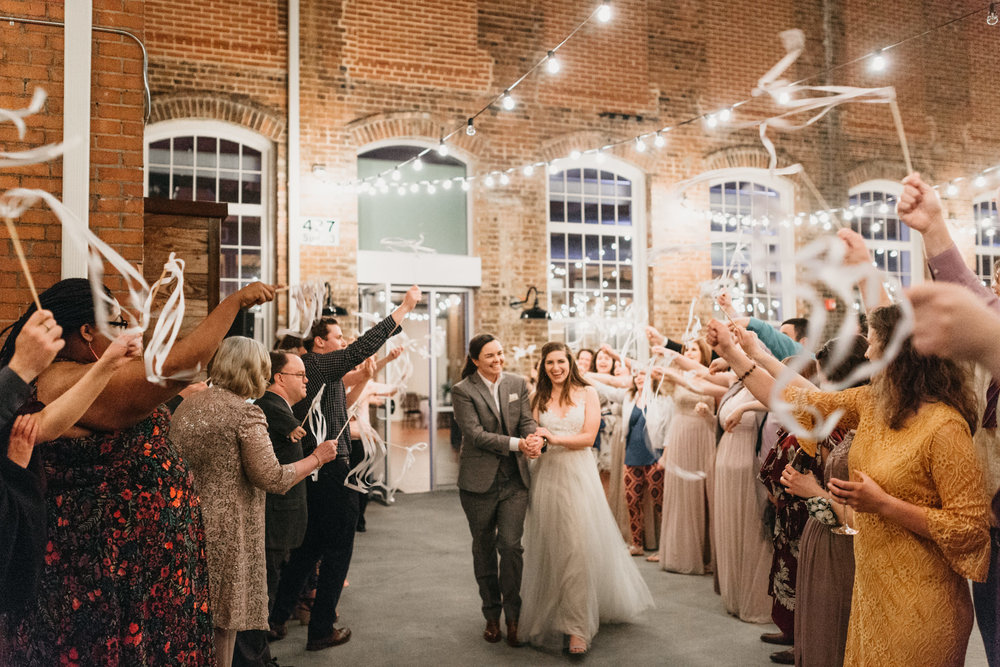 Ribbon send off for newlyweds at the end of their reception with string lights and guests in celebration.