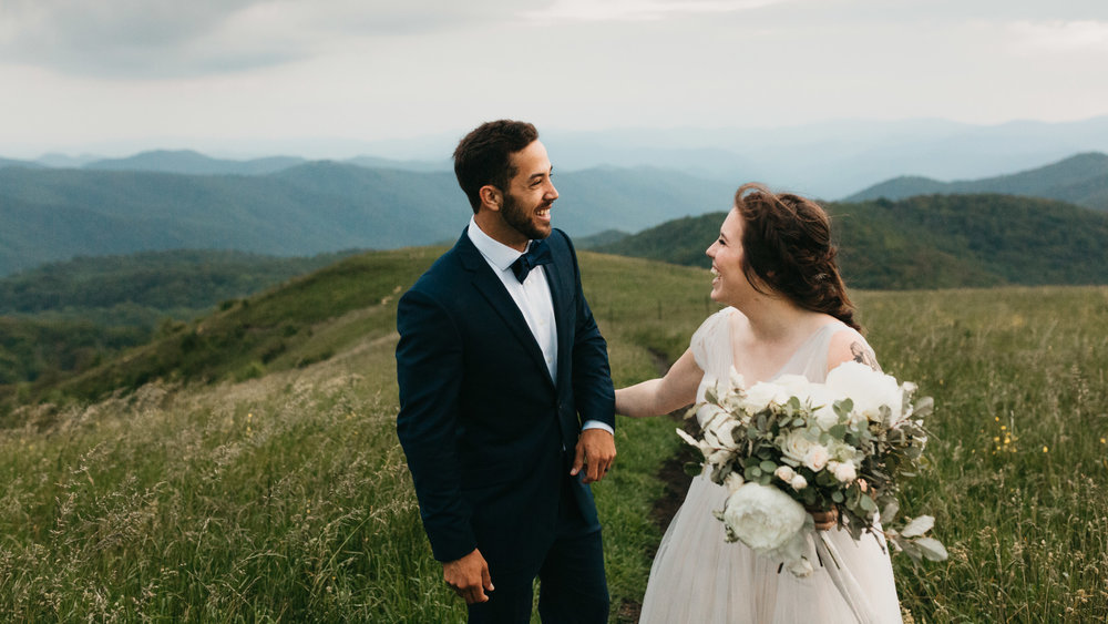 Bride and groom laughing and enjoying the beauty of the Blue Ridge mountains.