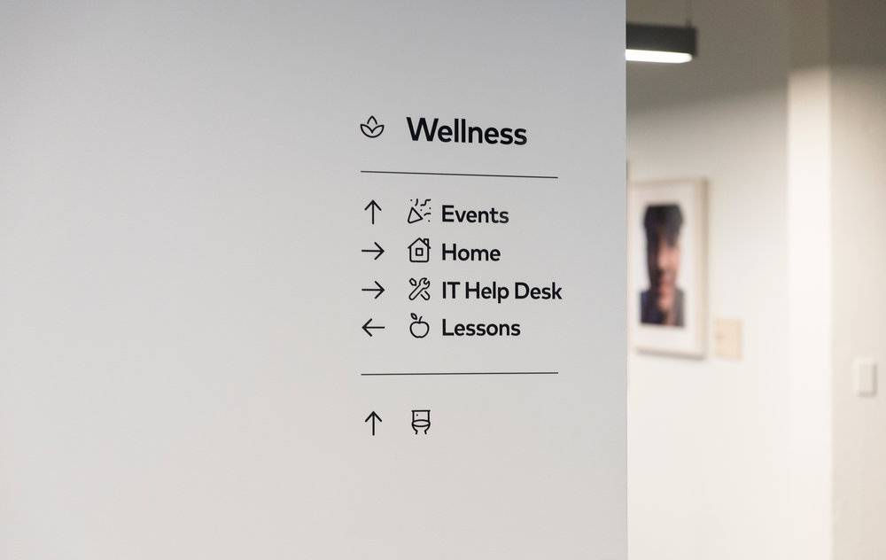 "The first layer of the directional signage is to help people find one of the 9 ""neighborhoods"" in the building. These meta level signs also direct to the nearest restrooms."