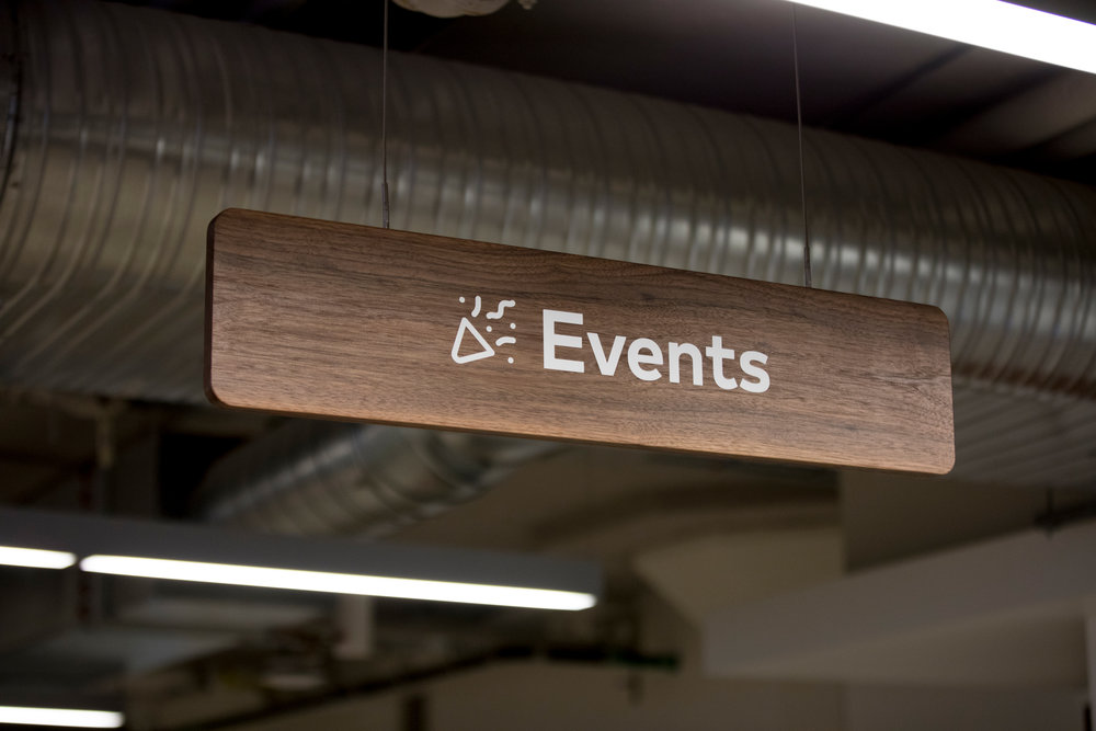 Each neighborhood also has solid walnut hanging signage featuring the name and associated icon.