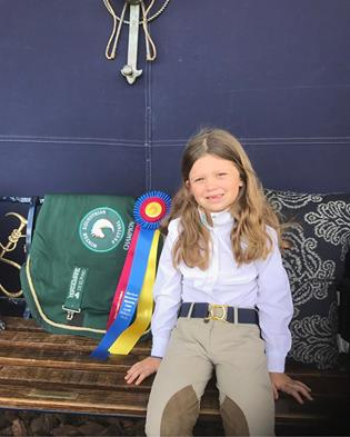 Elle models her Ruespari belt and her first WEF championship ribbon and cooler.
