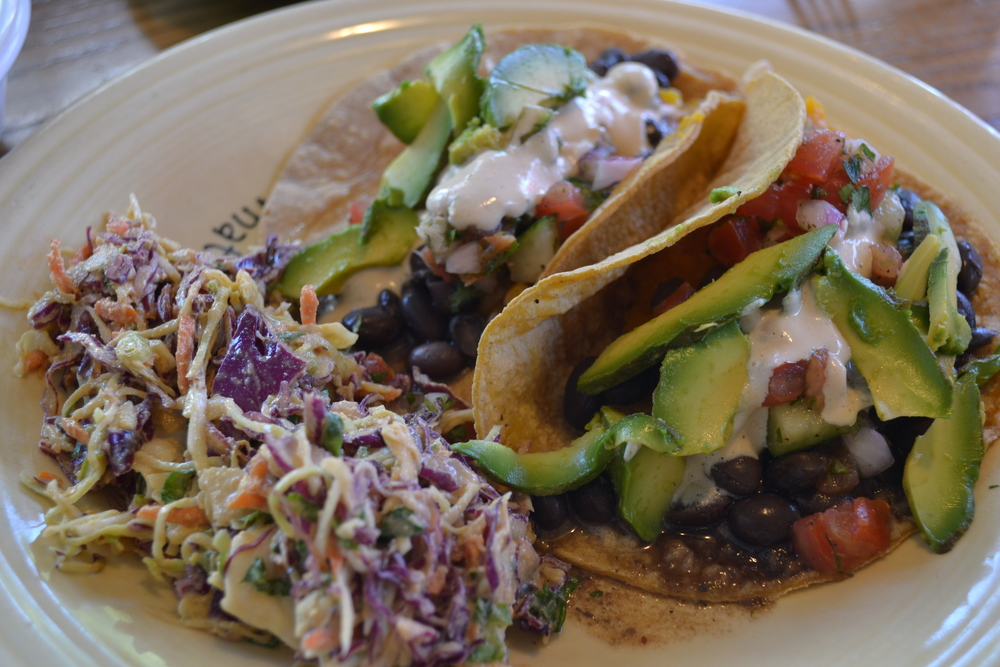 TRANSFORMED by two corn tacos stuffed with butternut squash, black beans, avocado and more, with a side of Mexican coleslaw.