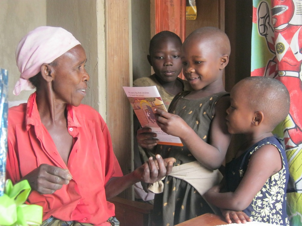 A grandmother and her grandchildren in Bushenyi District Uganda read an Uwezo report on learning outcomes. April 2012