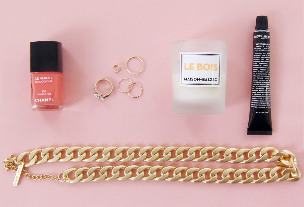From left to right: Chanel nail polish in Orange Fizz, Georg Jensen flower ring, BRVTVS ear cuff, Catbird alphabet ring and memory rings, Maison Balzac mini candle, Grown Alchemist Watermelon & Vanilla lip balm, 8 Other Reasons necklace.