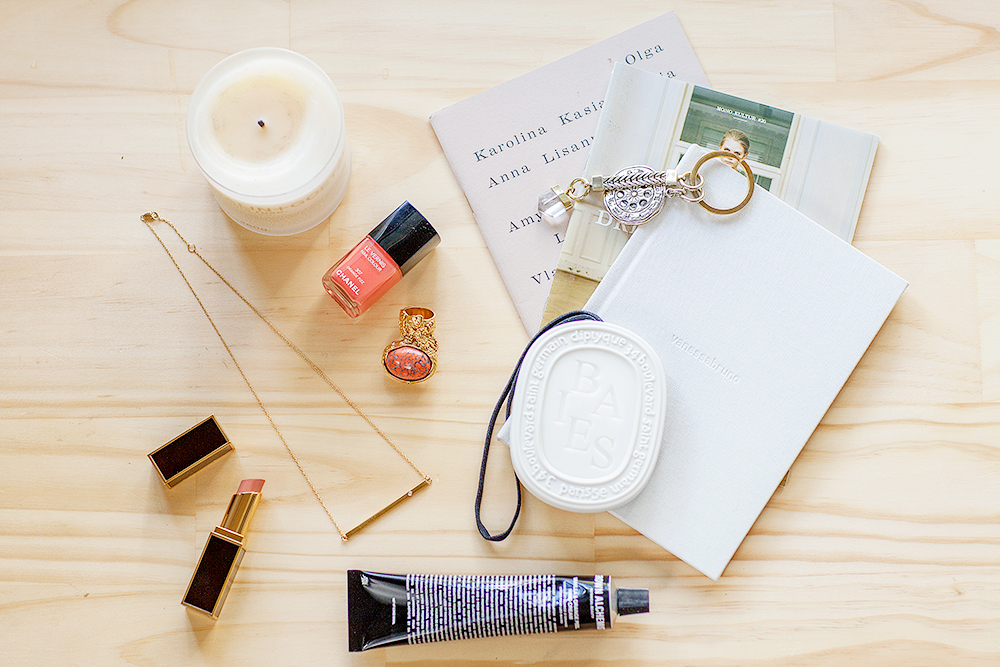 Clockwise from left to right: Malin + Goetz Rose candle, Holly & Kasia published by Ida Rhoda, Mono.kultur issue 20, Vanessa Bruno archive lookbook, Maniamania Moonphase keyring, Diptyque Baies scented oval, Grown Alchemist hand cream, Tom Ford Lip Shine in Abandon, Jennifer Zeuner 'Chelsea horizontal bar' necklace, Chanel Nail polish in Orange Fizz YSL Arty Oval ring in Coral