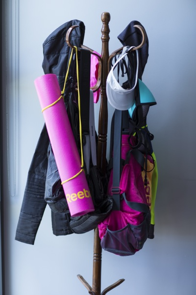 A hat rack in Bianca's bedroom holds running jackets, hats, bags and yoga mats