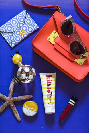 In her Sophie Hulme bag: Kit sunscreen, Karen Walker sunnies and Marc Jacobs scent