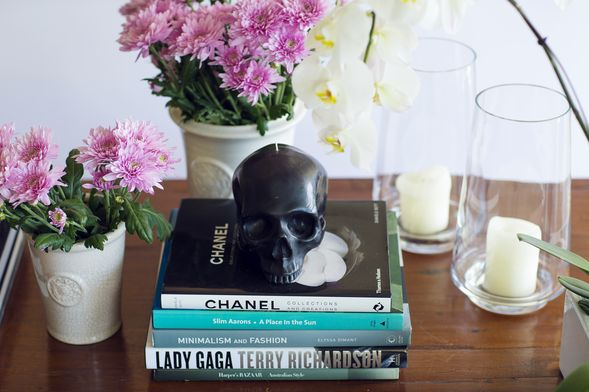 A beautifully styled coffee table features candles and fashion books