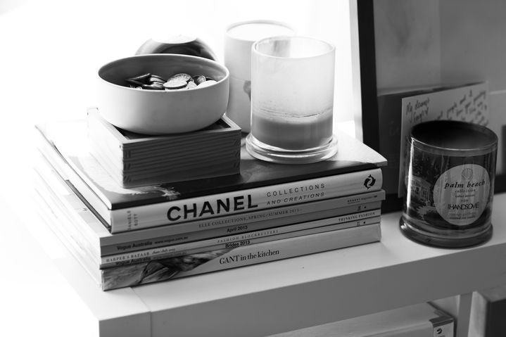 Coffee table books and more candles line the bookshelf