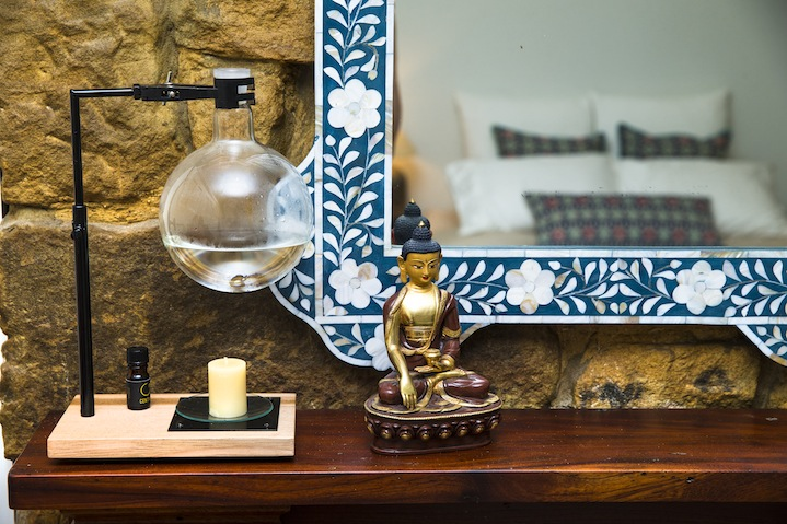 A unique oil burner and Buddhist statue takes pride of place in the bedroom.