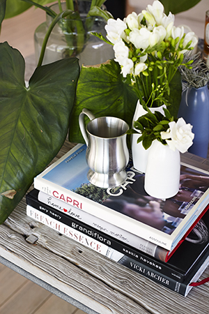 Coffee table books, flowers and ornaments decorate the designers house
