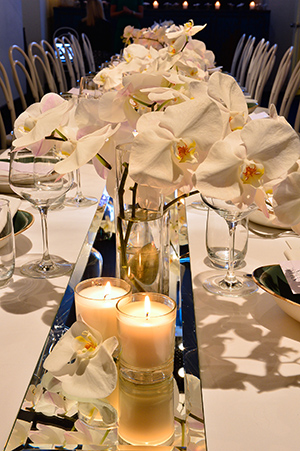 Flora and fragrances line the silver table runner
