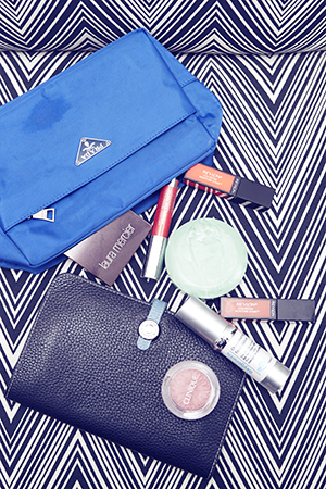 A Prada beauty bag and Hermes travel wallet keep Laura organised on the road