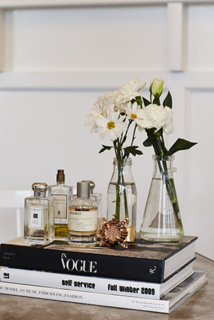 A stylish setting; books, bottles and beakers filled with flowers