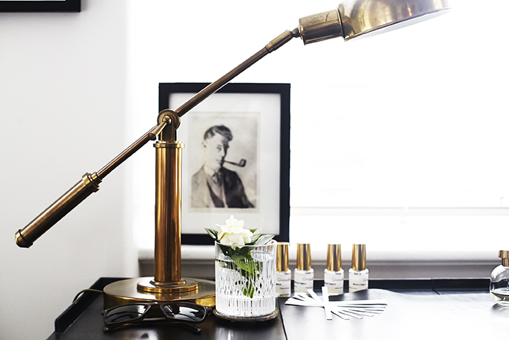 Meticulous desk details; a Scotch glass gains a floral touch and doubles as a vase