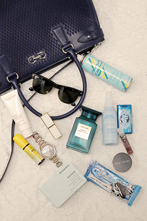 Erika's handbag essentials; a spray of Batiste dry shampoo, a swipe of Tom Ford lippie and golden accoutrements.