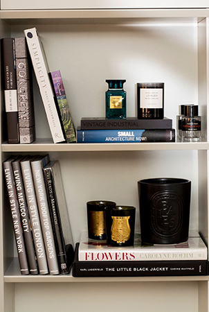 Coffee table books, perfumes and candles adorn the shelves
