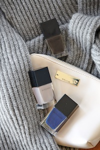 Indigo,grey and charcoal nail polish (available in-store only), cream zip up purse and luxepom pom scarf.