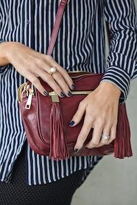Sigourney wears PETROL BLUEURBAN LONG SLEEVE SHIRT,dark red tasha cross body bag, Indigo nail polishand pearl ring.
