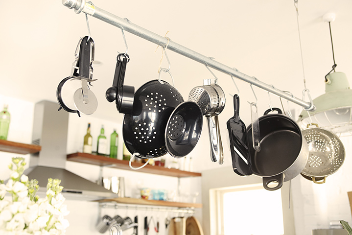 Pans and utensils hang from a bar above the kitchen workspace