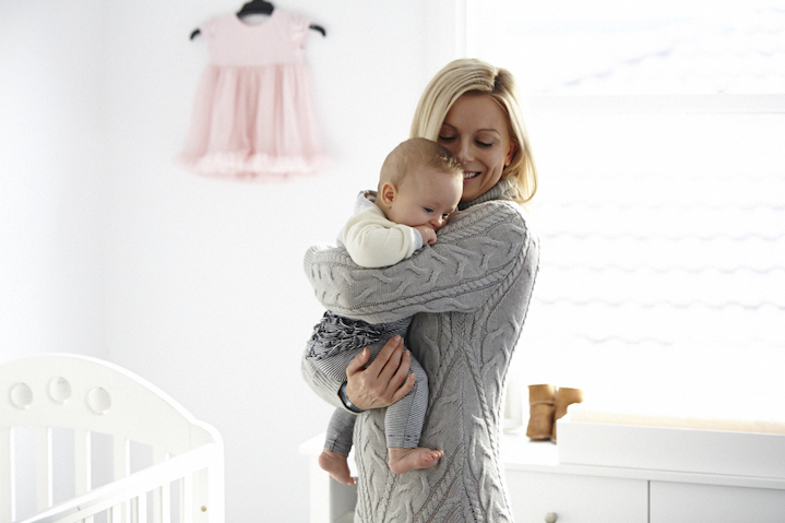 Emma, wearing a Blessed Are the Meek knit, settles baby Isla in her nursery
