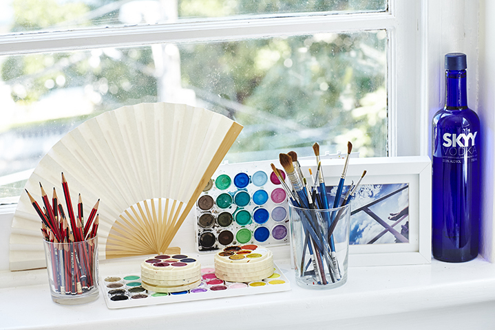 Pots of iridescent colour, brushes and pencils line the window of the illustrator's workspace