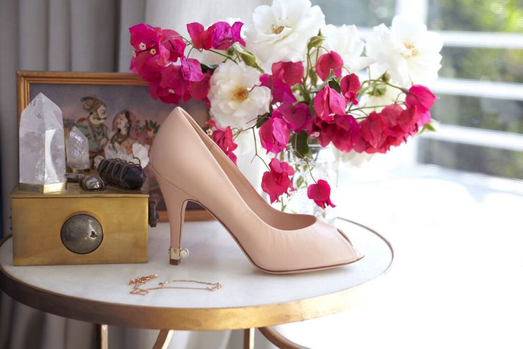 A beautiful marble table is home to flower arrangements, pastel heels, healing crystals,and fine jewellery