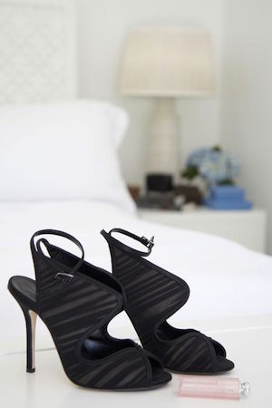 killer heels and a Dior lipstick in her crisp white bedroom