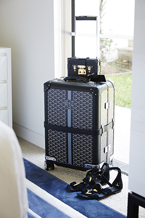 A monogrammed Maison Goyard suitcase sits pretty in Roxy's bedroom