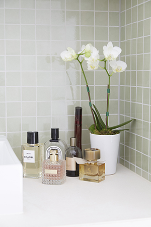A collection of Roxy's favourite scents and white orchids decorate her olive coloured bathroom