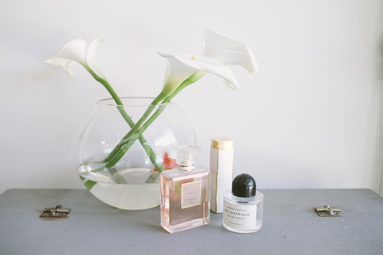 Crisp Calla Lilies sit atop a retro suitcase with her selection of French fragrance