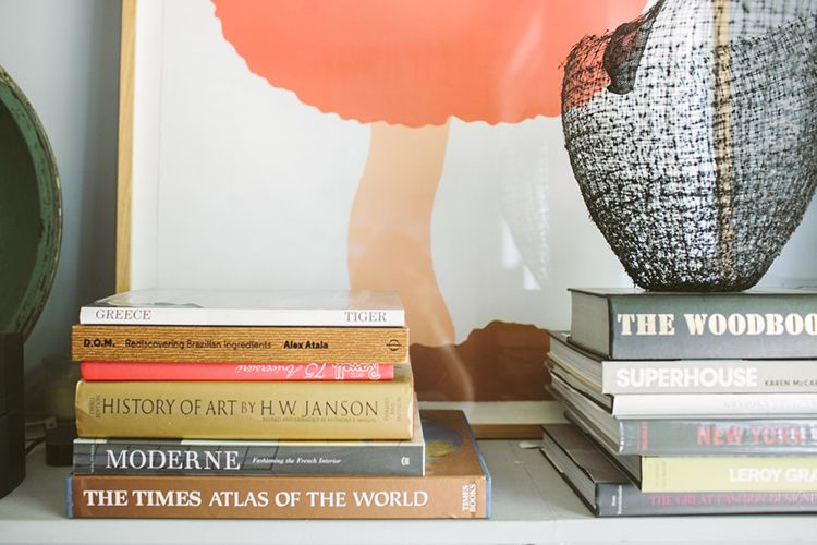 Piles of history and travel books pepper the space along with fabulous artworks