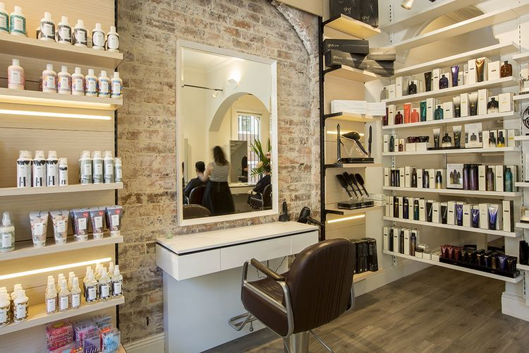 The salon is a mixture of exposed brick with cool undertones of white and marble for added edginess