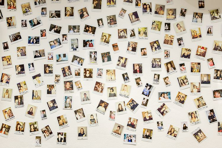 An array of client polaroids cover the walls