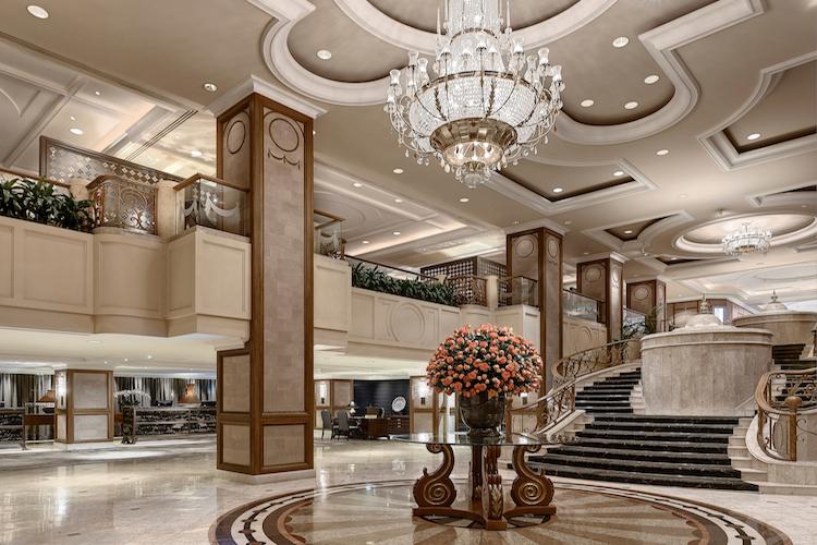 Glittering chandeliers sparkle overhead in the hotel foyer