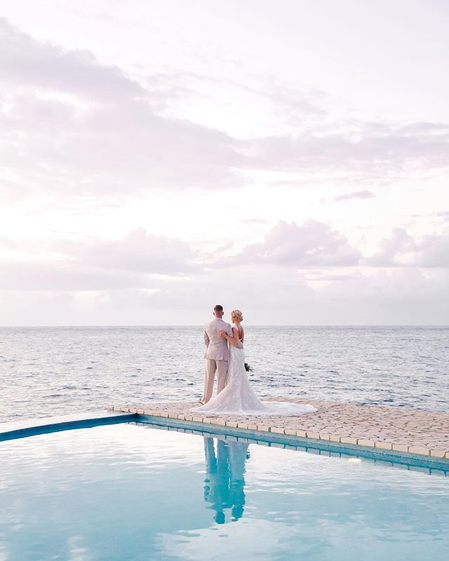 This Jamaican cliff-side wedding will have you grabbing your passports and sandals!⠀⠀⠀⠀⠀⠀⠀⠀⠀ It was so much fun photographing and filming Jayme and Niilo's wedding last December in Negril, Jamaica and we're excited that it's now featured on @caratsandcake. You can check out more from the link in our bio. • Venue: @rockhousehotel  Wedding Dress: @justinalexander  Bride's Shoes: @raphaellabooz  Bridesmaids Dresses: @misshayleypaige  Groom & Groomsmen Attire: @xedostyle  Hair: Denise Ayala and @lacey_does_hair  Makeup: @makeuptrisht  Invitations: @tasharaedesigns