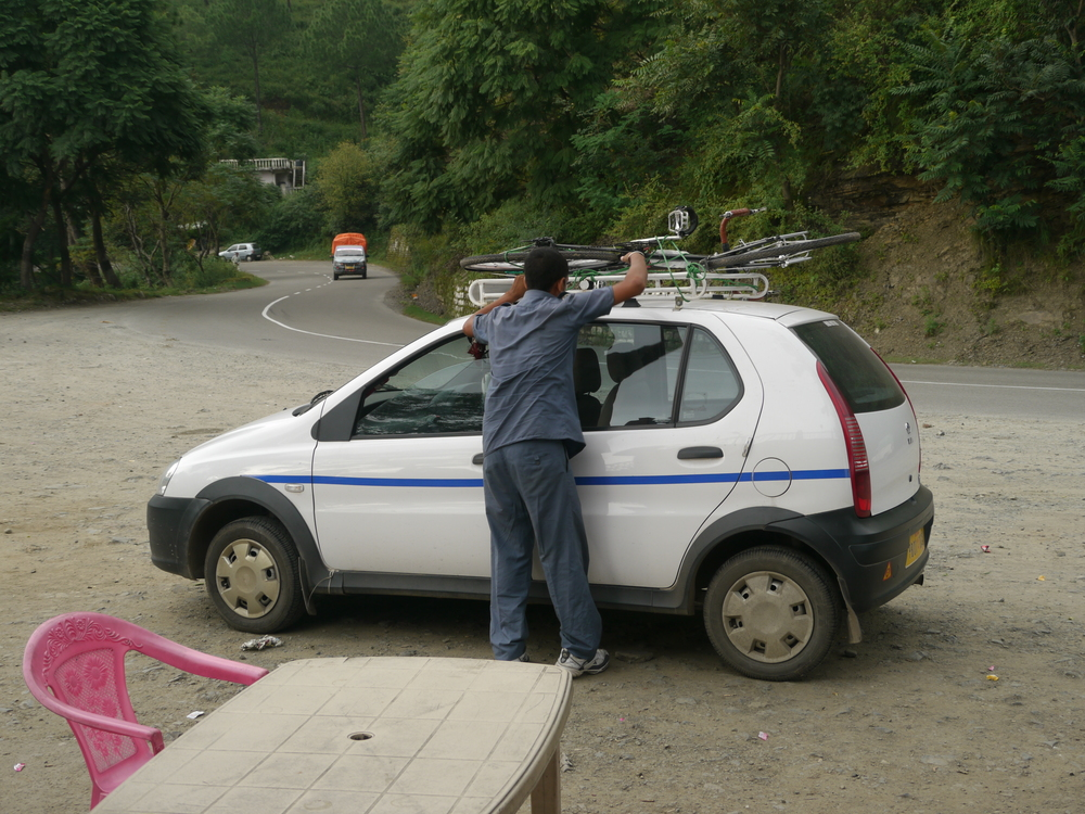 Here is my driver checking that the bicycle is loaded onto the roof securely at one of our stops for Chai.