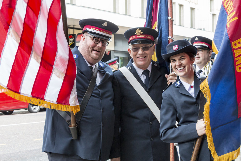 Bernie Dake and Sarah Muñoz of the STB with Gerald Turner (center) of the Boscombe Corps holding flags for the March of Witness.